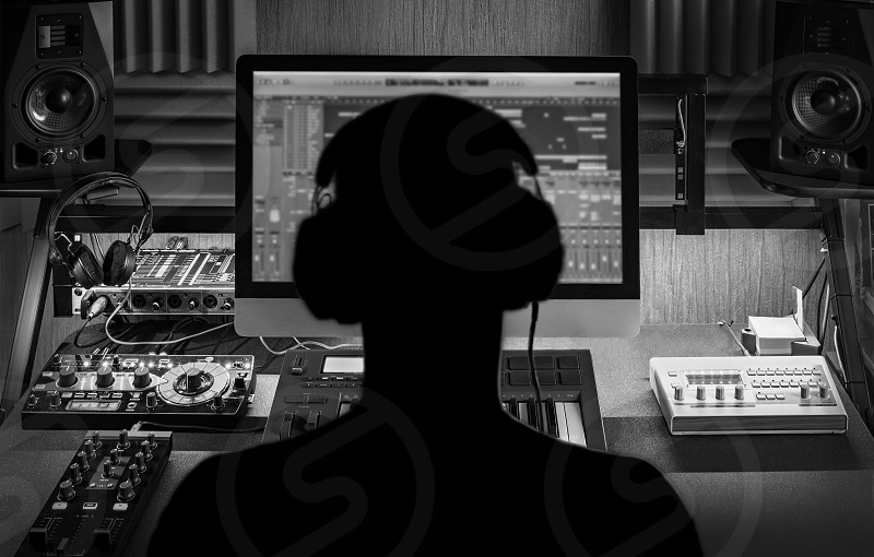 Man produce electronic music in project home studio. Silhouette. Black and white photo. photo