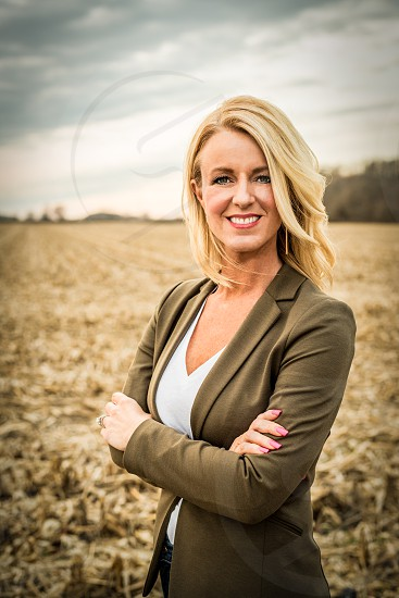 Portrait of woman standing outdoors in a field. Looking at camera. Business professional headshot. photo