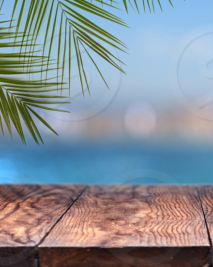 Empty wooden background over blurred background of a city with palm tree blue sky and bright sea water. Natural background with copy space. Can be used for display products. photo