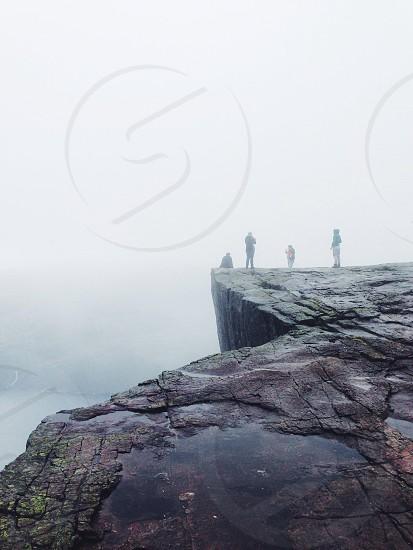 4 people on gray rock photo