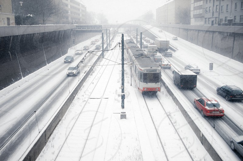 Blizzard snow on busy city highway with electrified tramway with inner city traffic and public transportation still flowing photo