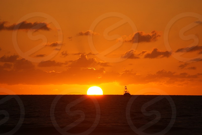 Orange sunset with boat silhouette  photo