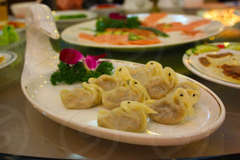 Chinese Food. Small little meat filled dumplings in the shape of ducks on a white duck platter. photo