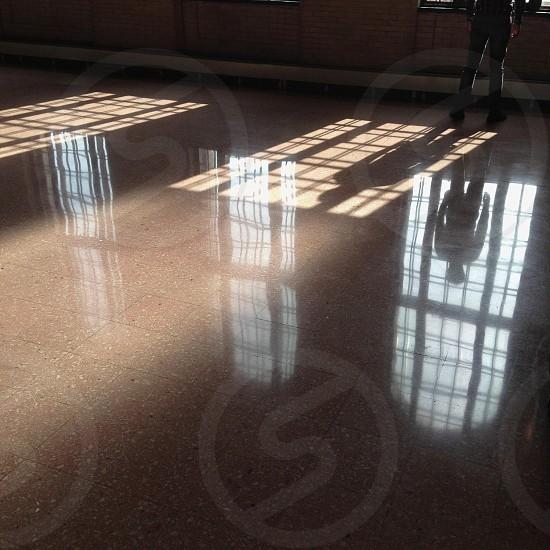 person standing on brown floor tiles near window photo