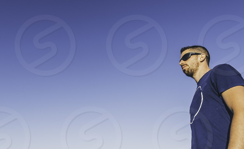 Young man with sunglasses and blue sky background photo
