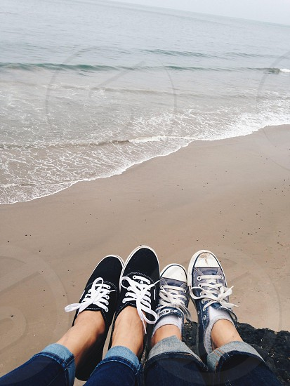 two people in denim converse shoes and cuffed blue jeans on beach photo