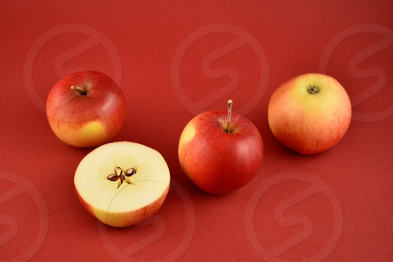 Red fresh apples. Apples on a red background. Sliced apple. Juicy apples photo