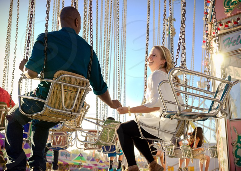 man and woman riding swings holding hands photo