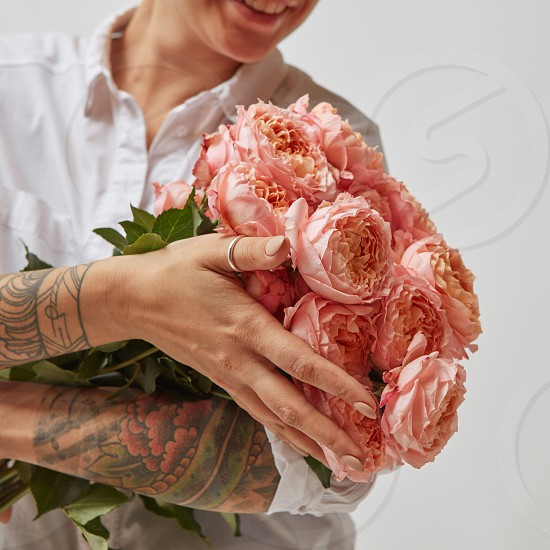 Smiling girl with a tattoo on her hands holding a bouquet of pink media roses on a gray background. Mothers Day photo