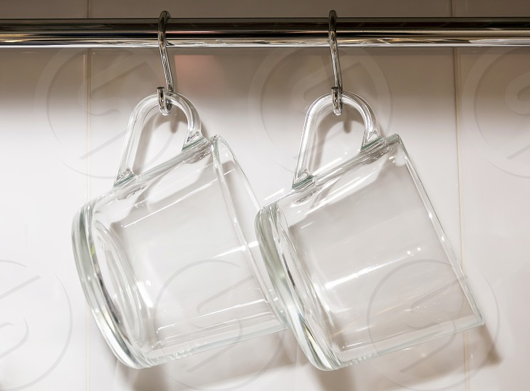 two glass transparent hanging mugs photo