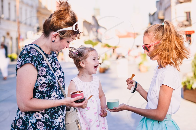 Family spending time together in the city centre enjoy eating ice cream on a summer day. Mother toddler and teenage girl spending quality time on sunny afternoon eating sweet dessert. Downtown area in the background photo
