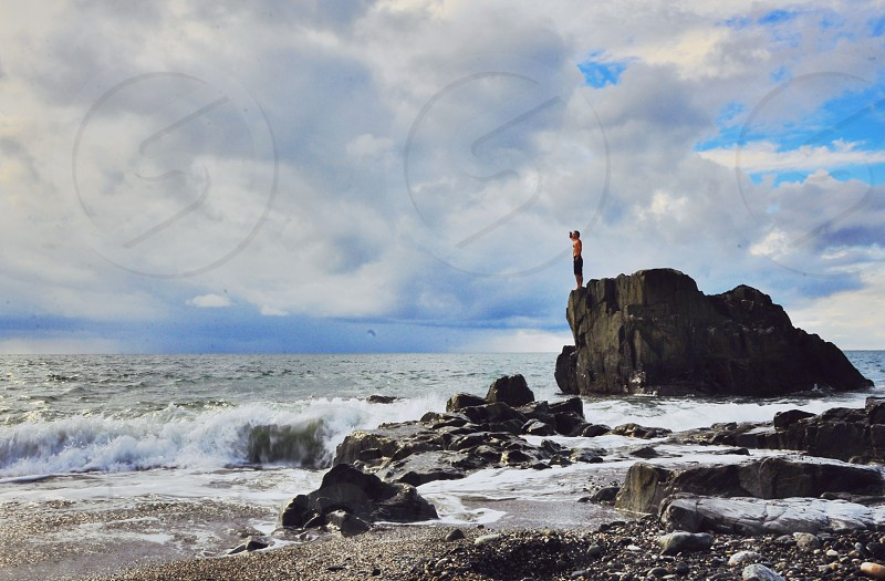 man on top of rock formation photo