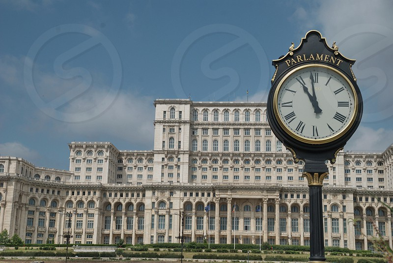Parliament building view with retro style public clock Bucharest Romania photo