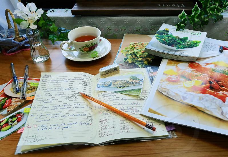 pencil on notebook near tea cup on table photo