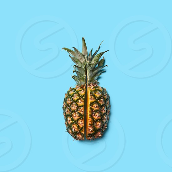 Pineapple with green leaves cut into pieces presented on a blue background with space for text. Creative layout for your ideas. Flat lay photo