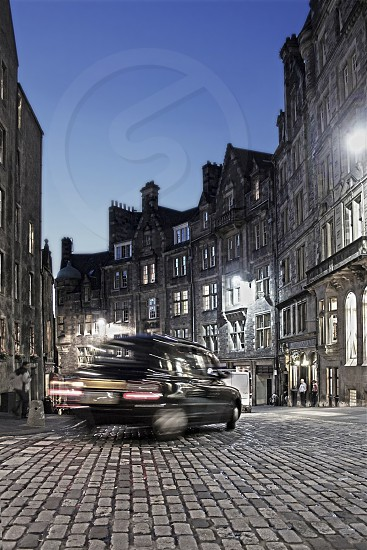 Night scene on Edinburgh's Cockburn Street with blurred cab in motion on cobblestones. photo