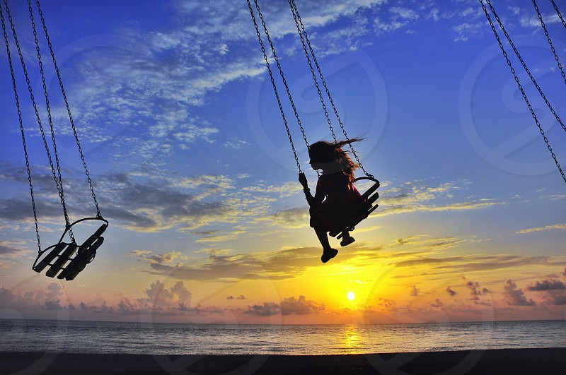 girl in red shirt riding on brown wooden swing photo