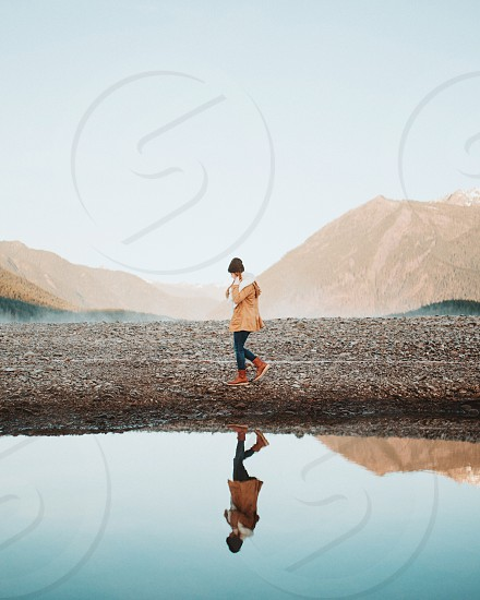 woman in brown jacket and blue denim jeans walking on brown rocky shore by lake under blue sky during daytime photo