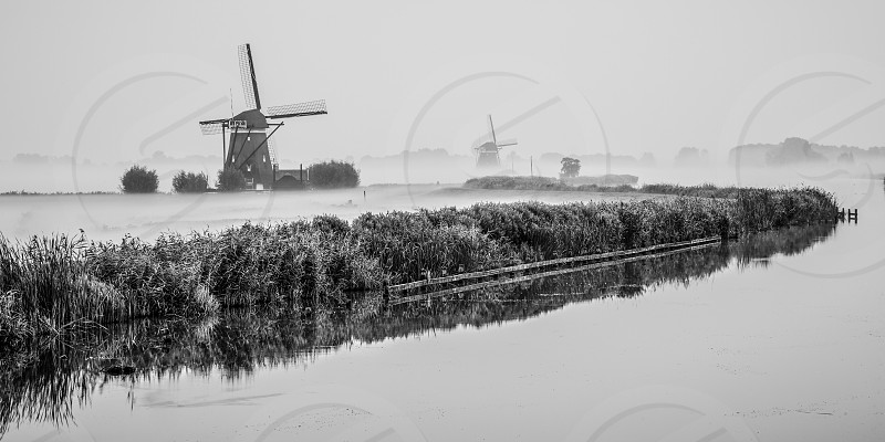 These two windmills are part of a Four in Row. This is a setup where four windmills were used (in the past) to remove overflowing water from a polder. The windmills in the photo are built in the Tweemanspolder near the village of Zevenhuizen in the province of Zuid-Holland The Netherlands. The mills are built approximately around 1722 and are part of Dutch heritage. photo