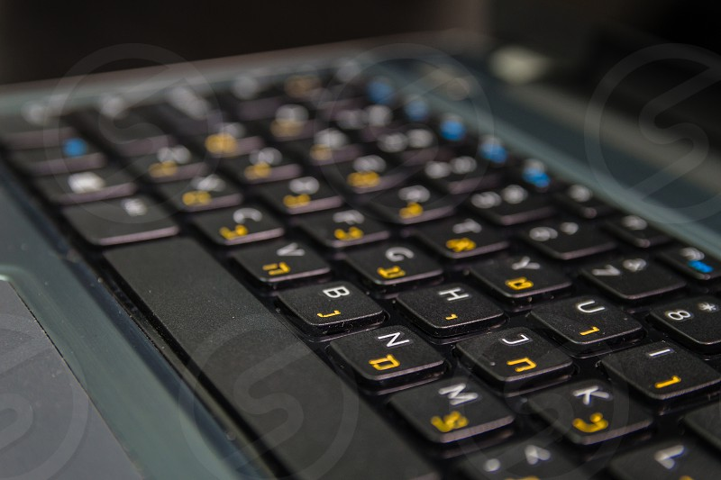 Keyboard with letters in Hebrew and English - Laptop keyboard - Close up photo