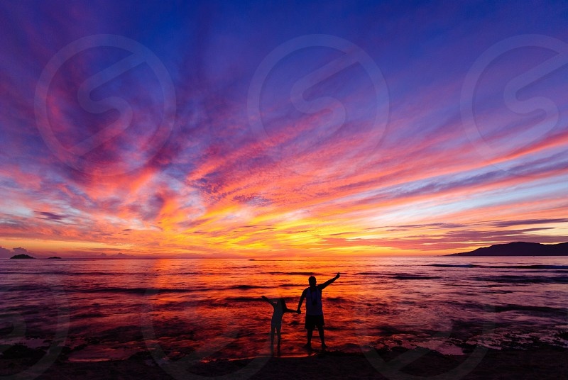 Travel sunrise beach sea shore coastal clouds enjoyment vacation adventure outdoor colorful display of colors relaxation relaxing morning walk family father and daughter photo