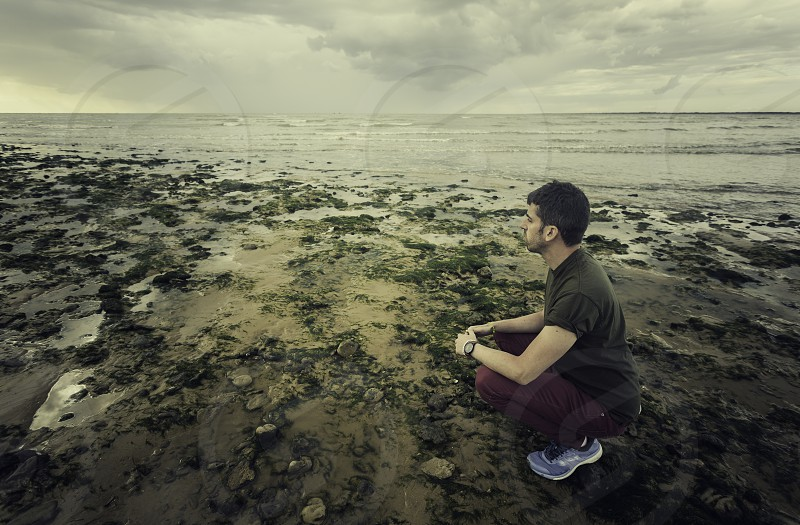 Young man with casual clothes and sneakers squatting on the shores of the Mediterranean sea between seaweed on the beach of Sanlucar de Barrameda photo