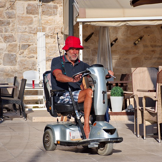 Portrait of senior man in electric wheelchair driving through the strits of Primosten in Croatia photo