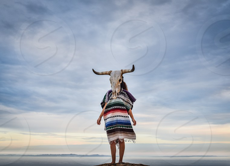 bullhead scull cow woman pancho mexican clouds sky portrait photo