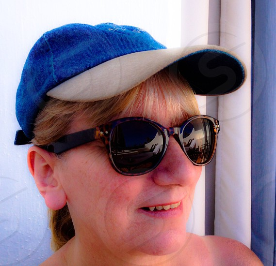 woman in black sunglasses and blue hat photo