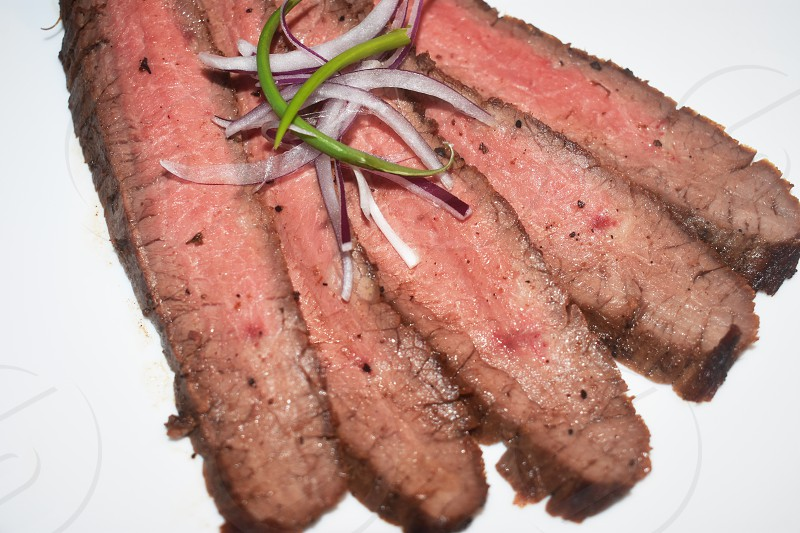 Medium rare slices of grilled flank steak adorned with scallions and onions on a white background photo