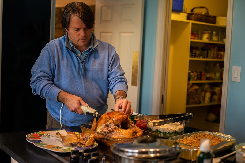 Father carving turkey on Thanksgiving photo