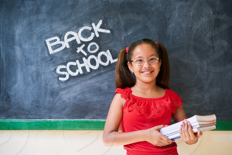 Concept on blackboard at school. Happy latina girl in class. Portrait of female child smiling looking at camera holding books. Back to school message photo