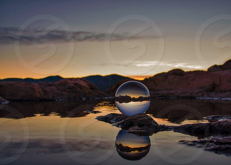 glass sphere on brown stone boulder photo