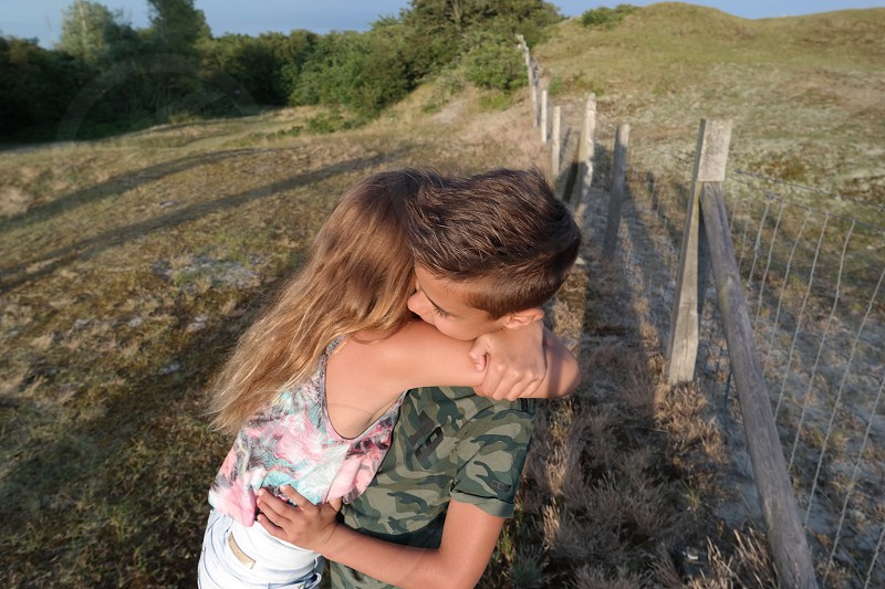 a boy in green and brown camouflage t shirt is being hugged by a girl in blue and pink floral tank top on the edge of a fence in a grassy area during daytime photo