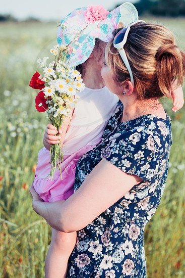 Mother and her little daughter in the field of wild flowers. Little girl picking the spring flowers for her mom for Mother's Day in the meadow. Girl handing the flowers to her mom. Nature scene family time photo