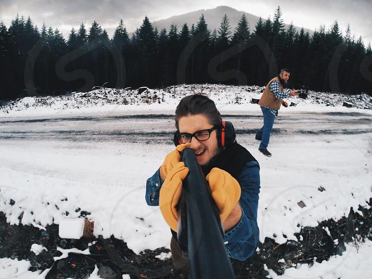 man in blue denim jacket holding black mono pod photo
