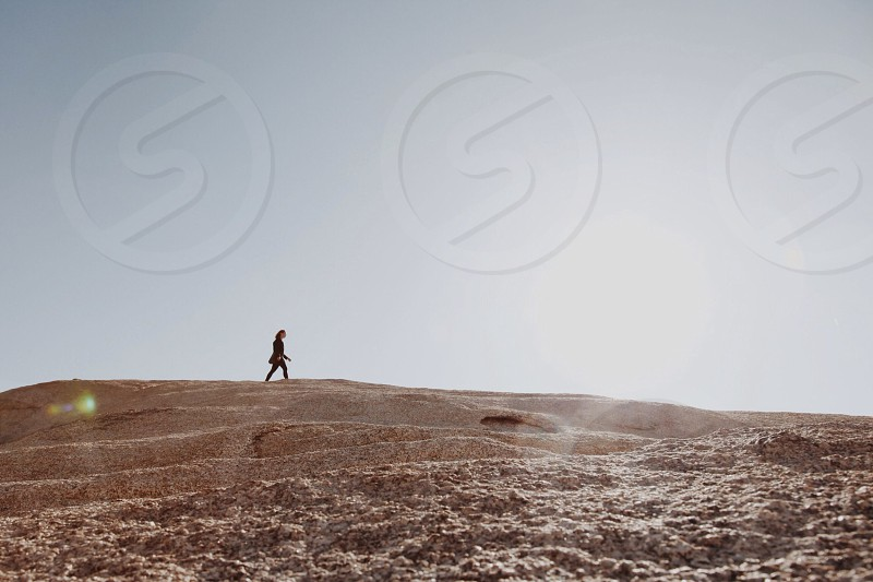 person in black pants walking beige sand photo