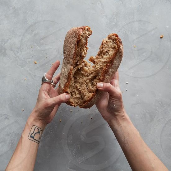 female hands holding a brown loaf of bread isolated on gray photo