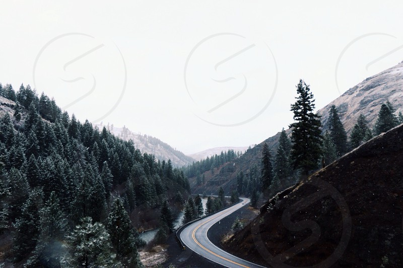 gray concrete winding road by mountain range with green trees under white sky photo