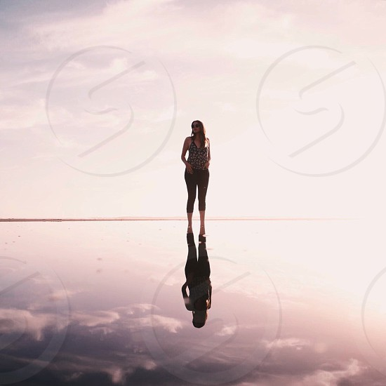 woman wearing tank top and black capri pants walking on salt flats below bright sky during daytime photo