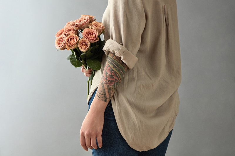 Young woman with a tattoo holds a bouquet of beige roses cappuccino on a gray background. Mother's Day Valentine's Day photo