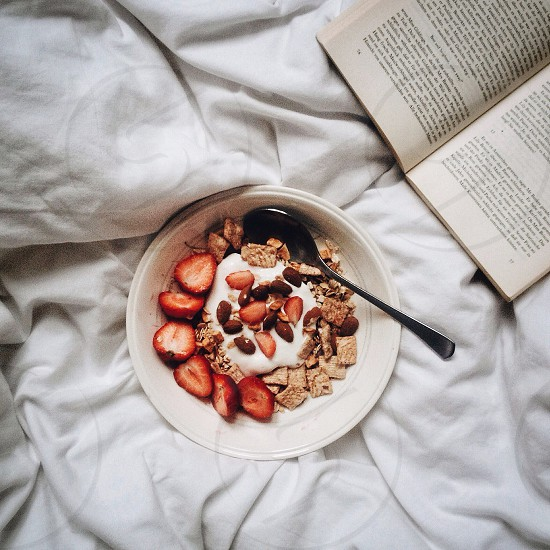 silver spoon on white bowl with sliced nuts strawberrys and oats photo
