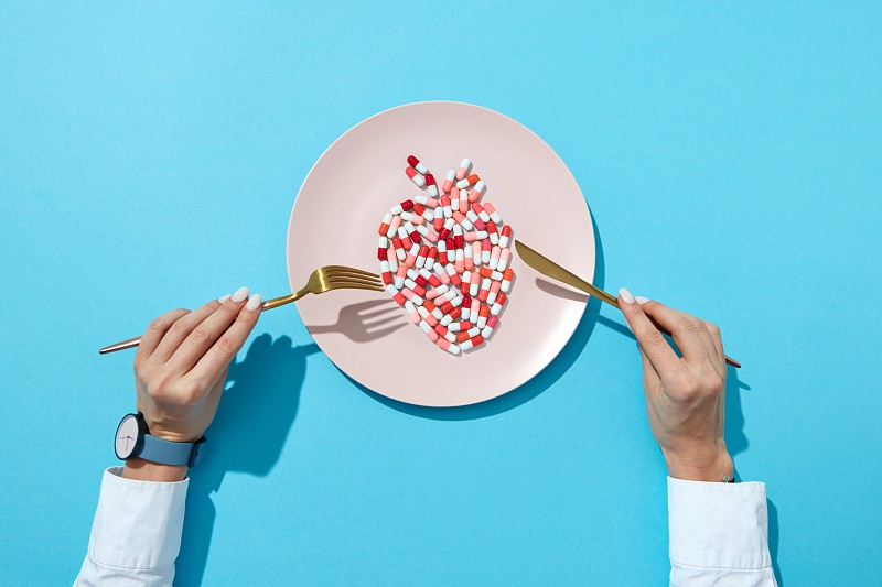 Fish from colorful pills and tablets on a white plate girl's hands with watch on a blue background with shadows copy space. The negative effect of pills on cardiovascular diseases. Top view. photo