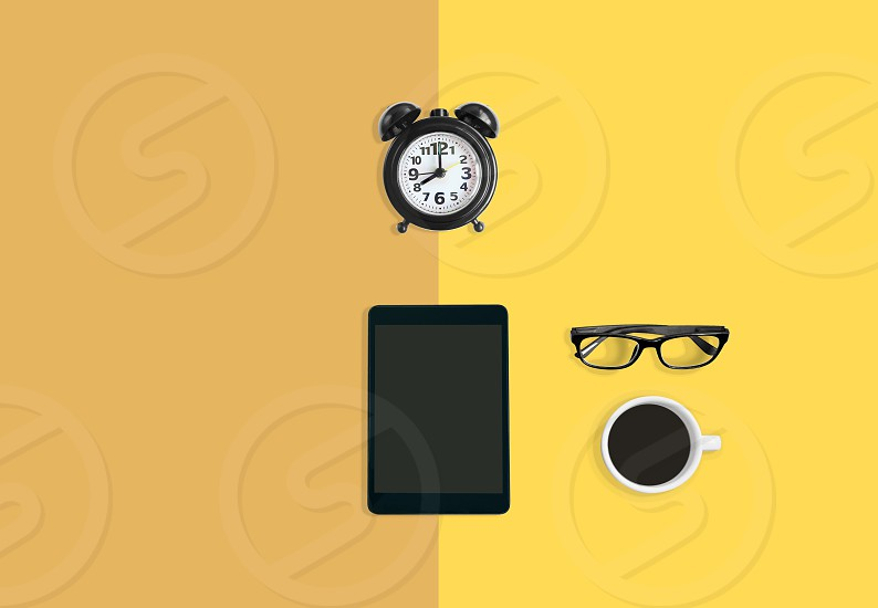 Modern home office workspace concept Black alarm clock A cup of black coffee eyeglasses and tablet on yellow pastel background with copy space photo
