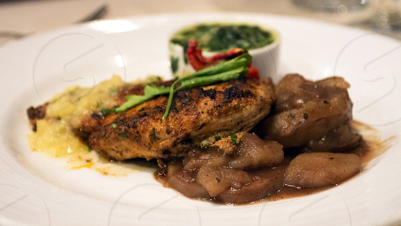Blackened supreme of spring chicken with scalloped potatoes and spinach souffle photo