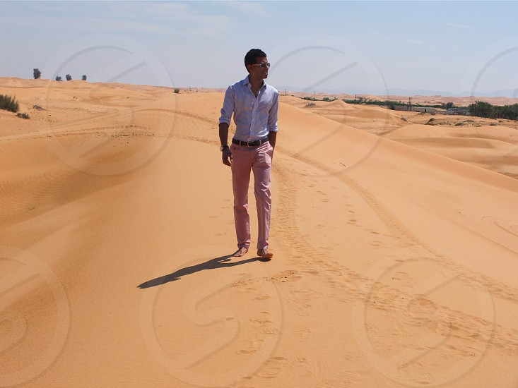 man in white dress shirt and pink pants walking on road photo