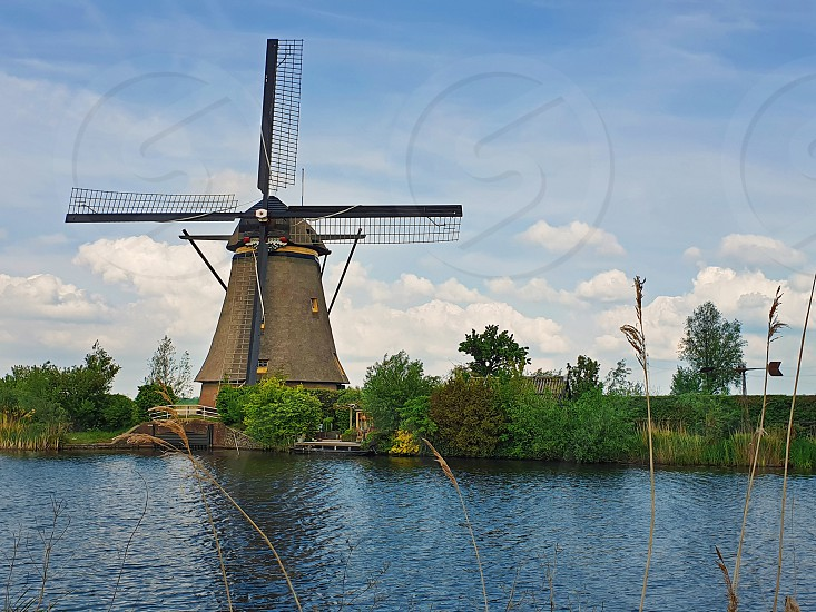 Old mill near a water canal at Kinderdijk Overwaard in the Netherlands. Windmill Unesco World Heritage with unique Dutch sight as popular tourist attraction in Holland. photo