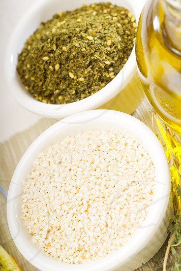 extra virgin olive oil and fresh  herbsthyme sesame seedsand zaatar spice blend on background photo
