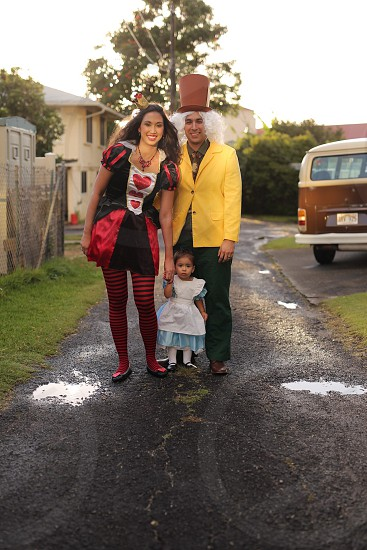 mother in the red queen father in the hatter and daughter in alice costume during daytime photo