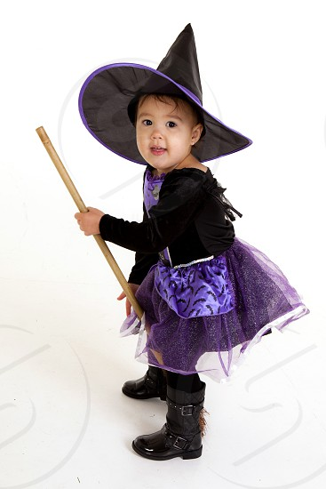 girl in witch costume standing and smiling photo